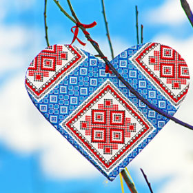 Hand made heart in the style of Ukrainian vyshyvanka on the handmade tree which children made due to Europe Day in Vinnytsia, Ukraine. Vyshyvanka is the colloquial name for the embroidered shirt in Ukrainian national costume. Vyshyvanka is distinguished by local embroidery features specific to Ukrainian embroidery
