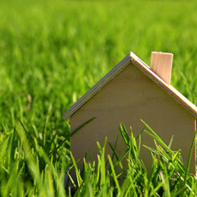 Image of vintage wooden toy house in the grass, garden or park at sunlight
