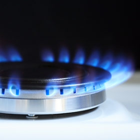 Closeup of gas stove with blue fire as background. Free space for text