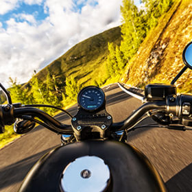 Detail of motorcycle handlebars. View from driver perspective, beautiful Alpine landscape in sunset light. Travel and sport photography in outdoor. Speed and freedom concept