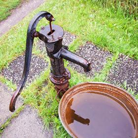 old wet cast iron water pump in garden