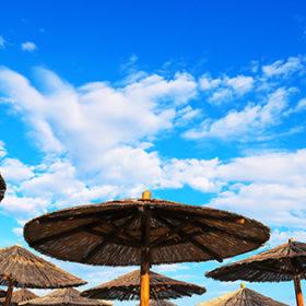 Brown straw beach umbrellas on a blue sky background. Summer beach holidays and travel, tropics. Adriatic Sea, Croatia
