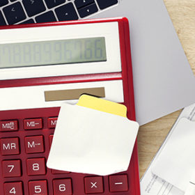Red calculator with note and utility bills bill on wooden table with copy space