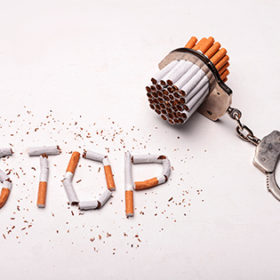Stop smoking. Close up of cigarettes bonding to human handcuffs. Isolated