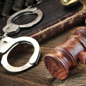 Real Handcuffs, Wooden Judge Gavel And Old Law Books On The Rough Brown Wooden Table Background. Arrest in the Courtroom Concept Or Release From Custody