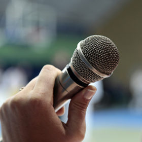 Image the announcer speaks into a microphone.