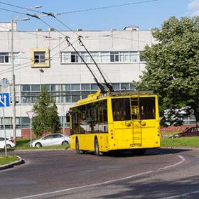 Yellow trolleybus on a city street. Transport