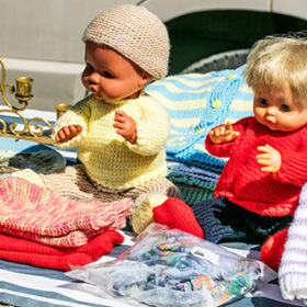 70s second hand plastic dolls with knitwear for knitting know-how display and childhood nostalgia at outdoor garage sale, flea market or street fair