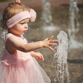 little girl plays with water in summer fountain