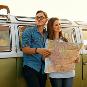 Tourist Man And Woman With Map In Nature Near Car. Happy Man And Beautiful Smiling Woman Using Map While Traveling On Summer Weekend Outdoors. Couple Travel On Sunny Day. High Quality Image.