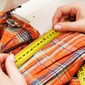 A sewer measuring a garment.