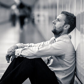 Young jobless business man suffering depression sitting on ground street underground leaning on wall alone looking desperate in Emotional pain Mental health Unemployment and Human emotions concept.