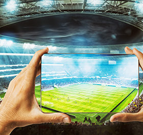 Hands hold a cellphone with a soccer stadium at the background