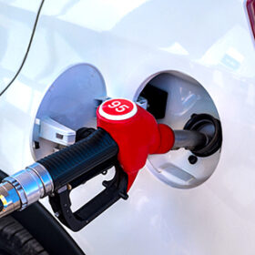 Refueling a car with fuel. A red fueling gun is installed in the gas tank of a white passenger car. On the gun the inscription means 95 gasoline.