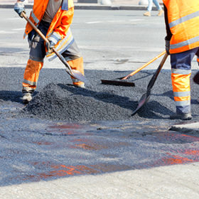 A working group of road workers in orange overalls renews a section of the road with fresh hot asphalt and levels it with shovels and metal slats.