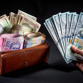 Pile of Ukrainian money in the wallet and american dollars in the hand on black background