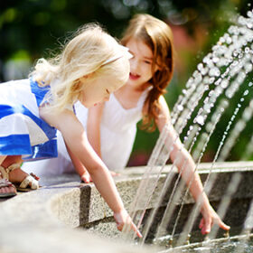 Two cute little girls playing with a city fountain on hot and sunny summer day
