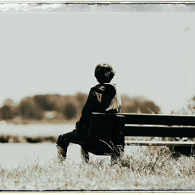 Old fashioned black and white photo of woman sitting on bench looking over water in summertime.