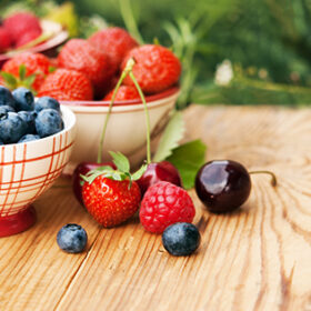 Berries in bowls on wooden table, fruits, cherry, raspberry, strawberry and bluberry