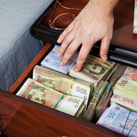 Hand reaches for the money in bedside table filled with Ukrainian cash