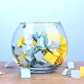 Pieces of paper for lottery in vase on wooden table on blue background