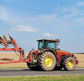 two tractors with ploughs - one on the road, another - in field