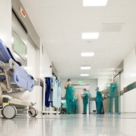 Blurred figures of people with medical uniforms in hospital corridor
