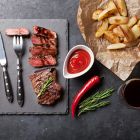 Grilled striploin steak with potato and red wine over stone table. Top view