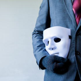 Business man carrying white mask to his body indicating Business fraud and faking business partnership.