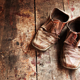 Old dirty brown leather shoes on wooden floor.