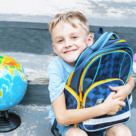 First-grader boy is sitting with a backpack on the doorstep of the school. bouquet and globe. the first bell. end of the school year