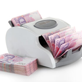 Machine for counting money with Ukrainian money, isolated on white