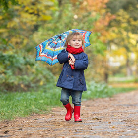 A small girl dressed in rubber boots and raincoats, holds an umbrella, laughs and runs through an autumn park.