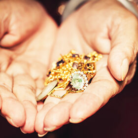 Gold ornaments in a hand with vintage filter effect.