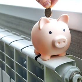The concept of paying for heating in homes with a cold climate. piggy bank pig on a white metal radiator. The concept of saving on utilities