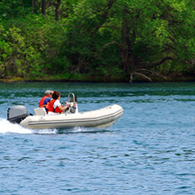 A couple driving an inflatable boat on a river