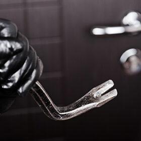 Crime scene - criminal thief or burglar hand in gloves holding metal crowbar break opening home door lock