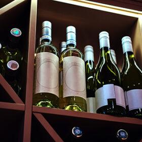 Bottles of tasty wine in posh reastoraunt are stored on the shelf.