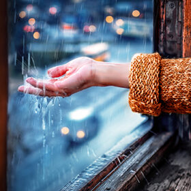 Woman checks by her hand the climate outside from the window. The raindrops cover her palm. The street with transport moving on the background. Horizontal view.