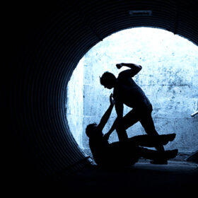Young man being mugged in a dark tunnel by a violent man