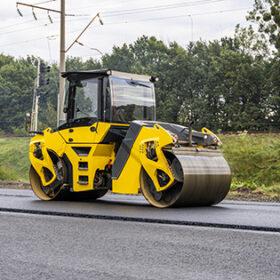Asphalt road roller with heavy vibration roller compactor press new hot asphalt on the roadway on a road construction site. Heavy Vibration roller at asphalt pavement working. Repairing