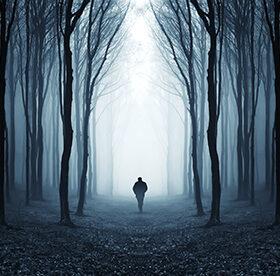 людина в темному лісі