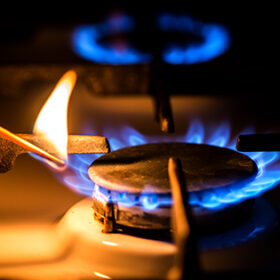 Hand with a match ignites the gas stove