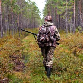 чоловік зі зброєю в лісі
