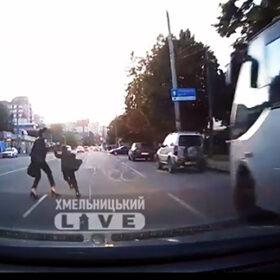 жінка з дитиною перебігають дорогу