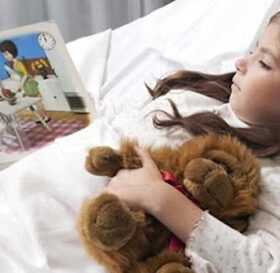 Girl lying in a hospital bed and reading a comic book