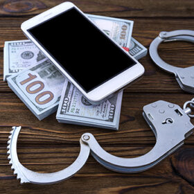 Concept phone scammers. Smartphone, money, handcuffs on a tree background. Crime, fraud, punishment, accession.