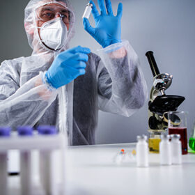 Scientist holding ampule with white powder, illegal pharmacy production, drugs. Laboratory assistant examines glass medical ampoule for injection. Penicillin dry powder medicine. Antibiotic injection.