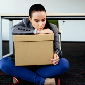 Photo of a depressed woman sitting on the floor after being let go from work